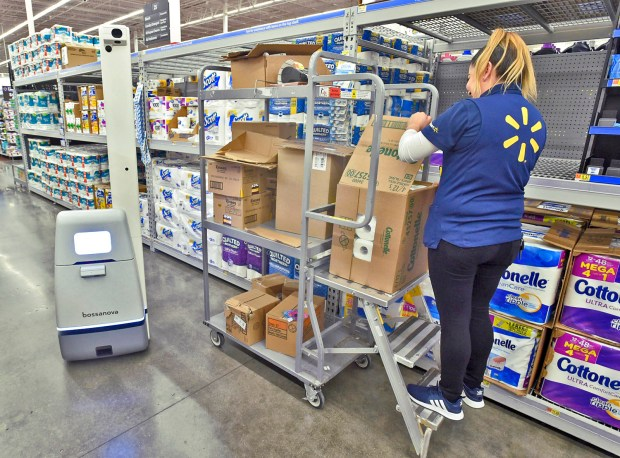 Walmart employee Sofia Ugalde stocks the shelves at the Burbank Walmart as the Bossanova robot senses her presence and veers to the side to avoid running into her. (Photo by Dan Watson)