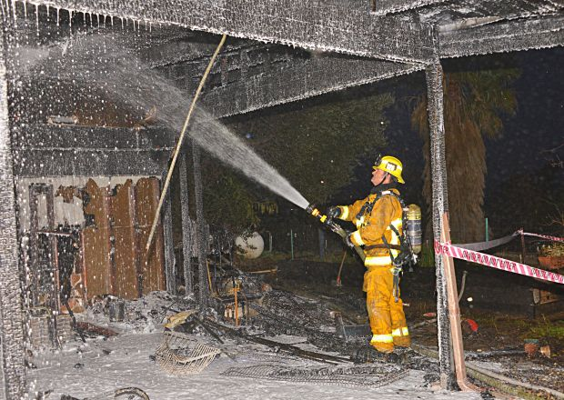 A firefighter puts water on a burned carport Tuesday, March 27, 2018, at a home near Chatsworth. (Photo by Rick McClure/Special to the Los Angeles Daily News)