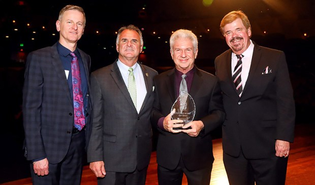 Musician Tom Ranier holds the Titan of Music award presented to the Cal State Fullerton grad by, from left, CSUF College of the Arts Dean Dale Merrill, CSUF President Fram Virjee and School of Music Director Larry Timm. (Photo courtesy of Cal State Fullerton)