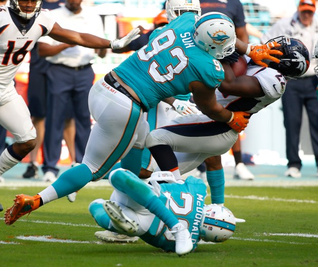 In this Dec. 3, 2017, file photo, Miami Dolphins defensive tackle Ndamukong Suh (93) and Miami Dolphins strong safety T.J. McDonald (22), tackle Denver Broncos running back C.J. Anderson during the first half of an NFL football game, in Miami Gardens, Fla. (Photo by Wilfredo Lee. The Associated Press)