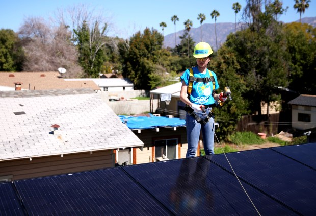 Magnolia Chinn, 18, a Freshman at Massachusetts Institute of Technology looks over a solar panel that she and other students installed along with nonprofit Grid Alternatives on the roof of an elderly person's home in Pasadena, Calif. on Wednesday, March 28, 2018. (Correspondent photo by Trevor Stamp)