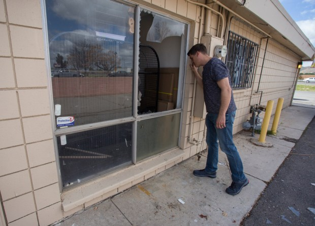 Erik Schreiner one of the owners of Birds-N-Paradise in Menifee inspects the hole left in a window at his store after burglars broke in and stole six parrots worth $8,950 early Friday, March 16, 2018. (Photo by Andrew Foulk, Contributing Photographer)