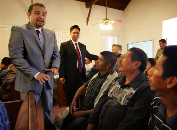 Billy Munoz, left, the new Guatemalan consul in San Bernardino, speaks with Iglesia Bautista Casa Blanca congregants and Guatemalan immigrants, sitting from left, Gabino Pedro Mateo, 50, Raymundo Martin Nolasco, 48, and Mateo Juan De Leon, during Sunday's service, on Feb. 8, 2015. Standing at center is Iglesia Bautista Casa Blanca pastor William Flores.