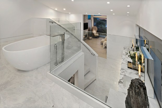 The second bath of this custom Cameo Highlands home features flowing marble and a Tony Duquette-designed mirror.