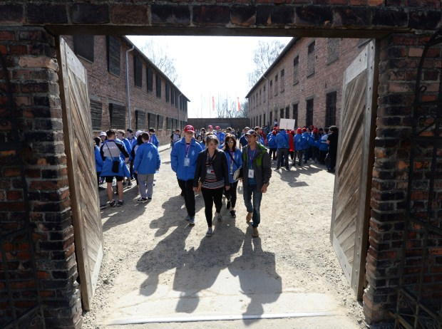 A group of young Jews visits the Death Wall at the former Nazi German death camp of Auschwitz ahead of the yearly March of the Living, a Holocaust remembrance march, in Oswiecim, Poland, on Thursday April 12, 2018. (AP Photo/Czarek Sokolowski)