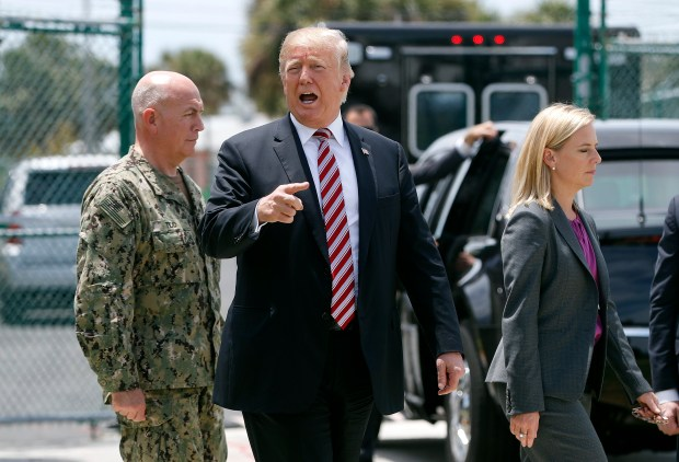 President Donald Trump, center, speaks to members of the media on Thursday, April 19, 2018, while walking with Homeland Security Secretary Kirstjen Nielsen, right, and Navy Adm. Kurt Walter Tidd, left, Commander of the U.S. Southern Command, during Trump's visit to Joint Interagency Task Force South anti-smuggling center in Key West, Fla., (AP Photo/Pablo Martinez Monsivais)