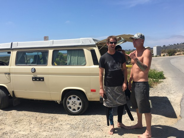Surfers Jacob Bennett, left, and Orion Taylor talk at the entrance of San Onofre State Beach while filing a police report after their van was broken into while they were surfing. (Photo by Laylan Connelly, SCNG)