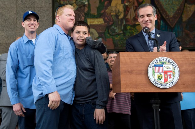 Sanitation worker Michael Adams hugs Jesse Hernandez, 13-years old, as Los Angeles Mayor Eric Garcetti stands at the podium and Kurt Boyer stands behind, during a press conference outside of City Hall to thank city workers for their efforts rescuing Hernandez.  City sanitation workers Boyer and Adams found and pulled out Hernandez after he fell into the sewer system while spending Easter at Griffith Park in Los Angeles. (Photo by Hans Gutknecht, Los Angeles Daily News/SCNG)