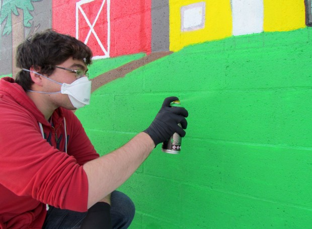 San Jacinto High School senior Giovanni Lomeli does touch ups to the spray-painted mural he and other students painted at Clayton A. Record Jr. Elementary School in San Jacinto. Photo by Diane A. Rhodes, contributing photographer