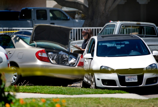 A Santa Ana Police Department Forensics specialist stands next to a car that was involved in a police chase the morning of . The gold sedan, left, was stolen in Anaheim and then located by LoJack in Santa Ana. The driver sped away from Santa Ana police and a chase ended with the car crashing into a tree and a Santa Ana police officer shooting a man in the car. A woman in the car was injured in the crash. Register file photo