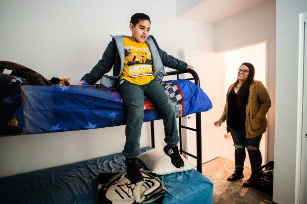 Robert Hernandez, 9, shows the bunk beds he shares with his brother in his bedroom during a tour with mom, Valerie Urias, right, at their new three bedroom apartment during the grand opening of Holt Family Apartments in Pomona on Monday, April 30, 2018. Clifford Beers Housing, a nonprofit dedicated to developing permanent supportive housing, dedicated the new Holt Family Apartments as part of PomonaÕs solution to the areaÕs homelessness crisis.(Photo by Watchara Phomicinda, Inland Valley Daily Bulletin/SCNG)