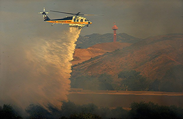 A water-dropping helicopter attacks a brush fire Sunday, May 6, 2018, near Route 126 and west of Six Flags Magic Mountain. Crews continued battling the blaze on Monday. (Photo by Rick McClure/Special to the Los Angeles Daily News)
