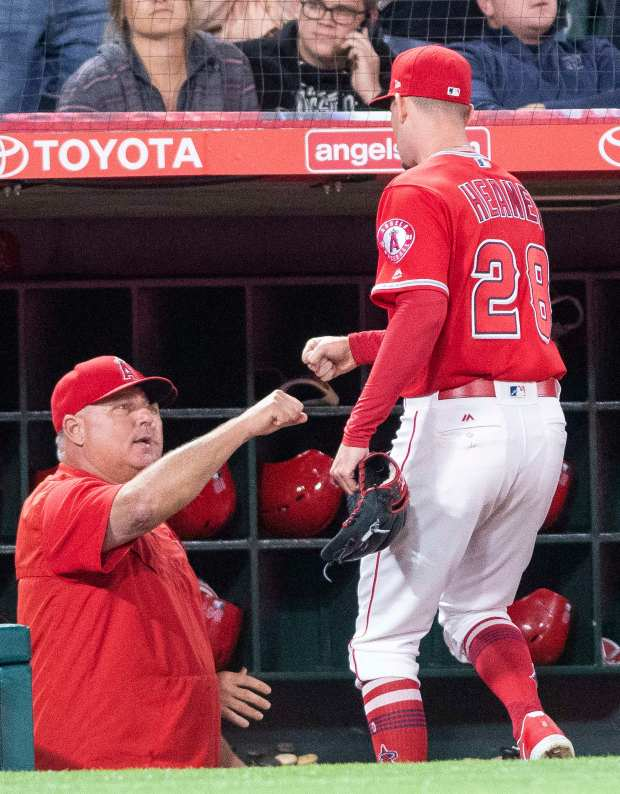 Mike Scioscia, seen giving a fist bump to Angels starting pitcher Andrew Heaney, right, is within four victories of surpassing mentor and former Dodgers manager Tommy Lasorda in career managerial wins. (Photo by Paul Rodriguez, Contributing Photographer)