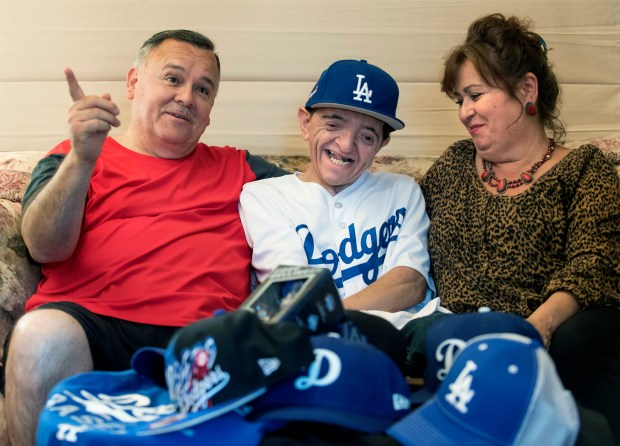 Michael Cadena is flanked by his parents, Joe and Sylvia in their Riverside home behind a pile of Dodgers swag given to Micheal by the community after learning that he was bullied and his Dodgers hat was stolen. (Photo by Cindy Yamanaka, The Press-Enterprise/SCNG)
