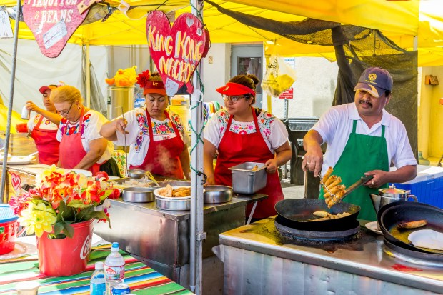 The crew of Olvera Street Taquitos & Tamales cooks up specialties at Fiesta Hermosa in Hermosa Beach on Sunday. (Photo: Gil Castro)