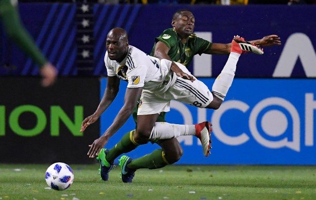 Galaxy defender Michael Ciani falls as he goes after the ball with Portland's Fanendo Adi on March 4 at StubHub Center. (Mark J. Terrill/The Associated Press)
