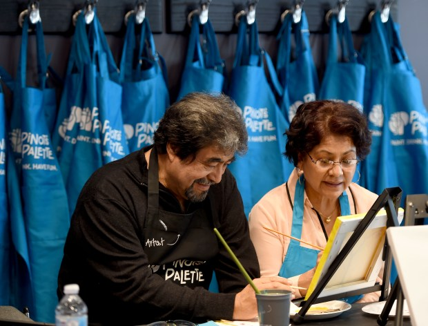 Gustavo and Yolanda Ochoa work together creating a masterpiece at Pinot's Palette, a new spot in Long Beach that mixes a wine bar with an art class. The shop is part of growing franchise and they held a grand opening at the 470 Pine Avenue location in Long Beach on Saturday, May 26, 2018. (Photo by Brittany Murray, Press Telegram/SCNG)