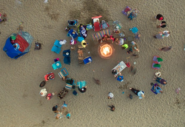 Beach goers gather around a fire pit at Bolsa Chica State Beach in Huntington Beach on June 18, 2015. Jeff Gritchen, staff photographer.