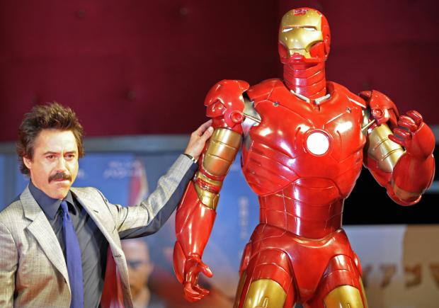 "Robert Downey Jr. poses by a life-size Iron Man model during a press conference on Sept. 3, 2008, in Tokyo for the first ""Iron Man"" movie. The suit that Downey wore in the movie is missing from a Pacoima warehouse. (Photo by TOSHIFUMI KITAMURA/AFP/Getty Images)"