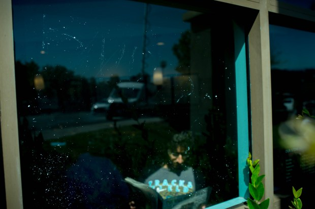 "A customer reads in Starbucks where the remnants of a ""BNR??"" tagging can be seen on Wednesday, May 16, 2018, in La Canada Flintridge. A Starbucks patron received two coffee cups with the term ""Beaner"" on Tuesday. (Photo by Sarah Reingewirtz, Pasadena Star-News/SCNG)"