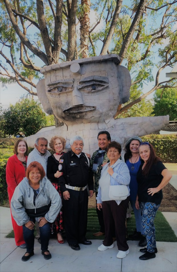 """Standing in front of Martin Sanchez's sculpture, """"Pretty Lady Ambassador,"""" are, from left: Frances Vasquez, Charles Mendoza, Dora Harmon, Morris Mendoza, Ernie Benzor, Esther Chavez, Rose Monge and Lillian Solorio. Scharlett Stowers Vai is bowing in the front row. (Photo courtesy of F. Vasquez)"""