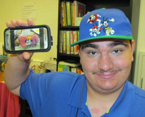 "Jared Thomas, an 18-year-old Beaumont resident, shows a photo of the rock he painted of Dot Warner from the ""Animaniacs"" cartoon, one of his favorite characters.Photo by Diane A. Rhodes, contributing photographer"
