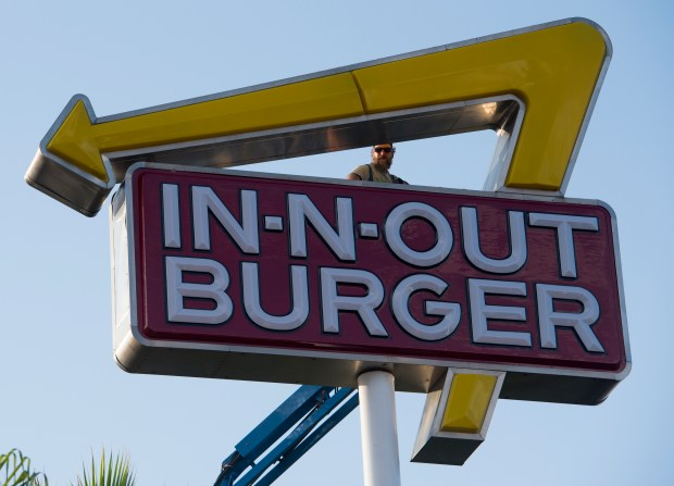 A worker on a cherry picker works on an In-N-Out Burger sign in Westminster Thursday morning.in Santa Ana, CA on Thursday, August 31, 2017. (Photo by Sam Gangwer, Orange County Register/SCNG)