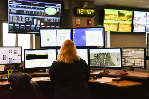 FILE - In this March 15, 2018, file photo, a dispatcher works at a desk station with a variety of screens used by those who take 911 emergency calls in Roswell, Ga. Apple is trying drag the U.S.'s antiquated system for handling 911 calls into the 21st century. If it lives up to Apple's promise, the iPhone's next operating system will automatically deliver quicker and more reliable information pinpointing the location of 911 calls to about 6,300 emergency response centers in the U.S. (AP Photo/Lisa Marie Pane, File)