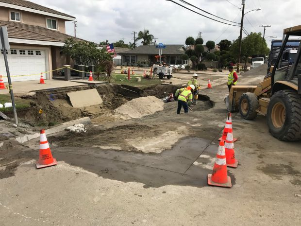 A woman swerving to avoid an oncoming car sheered-off a utility pole and fire hydrant, damaging a water main and causing a 20-foot sinkhole at about 9:50 p.m. Saturday, June 16, 2018, at Rieves Avenue and Brunache Street in Downey, CA. Workers continued to do repairs on Monday morning, June 18, 2018. (Photo by Nathaniel Percy, Lon Beach Press-Telegram)