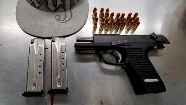 Pomona Police on Saturday said a known gang member was arrested after a vehicle and foot chase in which he climbed over a fence into a rear yard, injuring his knee upon landing. He had tossed a loaded gun a few feet from where he was injured, police said. Police recovered the weapon. Photo courtesy Pomona Police Department.