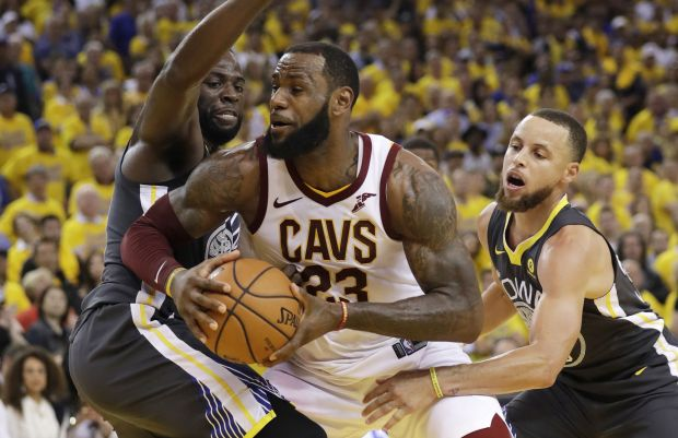 Cleveland Cavaliers forward LeBron James, center, is defended by Golden State Warriors forward Draymond Green, left, and guard Stephen Curry during the second half of Game 2 of basketball's NBA Finals in Oakland on Sunday, June 3, 2018. James and Curry are among the players who say they won't go to the White House if their team wins the championship. (AP Photo/Marcio Jose Sanchez)