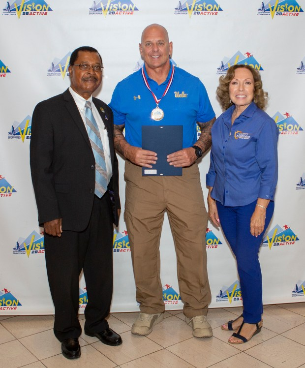 Action Hero Mark Geletko stands with Dr. Maxwell Ohikhuare, left, and 5th District Supervisor Josie Gonzales, right, at the Vision2BActive awards ceremony in San Bernardino. (Courtesy photo)
