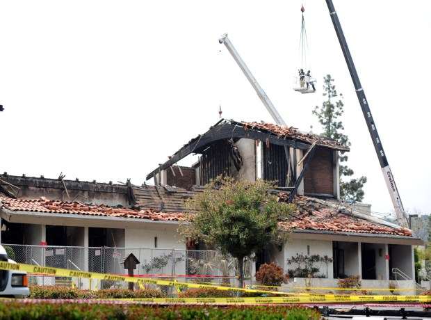 File photo of investigators looking over St. John Vianney Catholic Church as Los Angeles County Sheriff's and FBI investigators process the scene suspected of arson in Hacienda Heights on Tuesday, April 19, 2011. St. John Vianney Catholic Church burned shortly after midnight Saturday night. Damages are estimated at about $8 million. (SGVN/Staff Photo by Keith Birmingham/SVCITY)