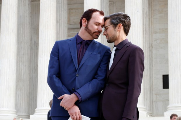 In this Dec. 5, 2017 file photo, Charlie Craig, left, and David Mullins touch foreheads after leaving the Supreme Court in Washington. The Supreme Court is setting aside a Colorado court ruling against a baker who wouldn't make a wedding cake for the same-sex couple. (AP Photo/Jacquelyn Martin)