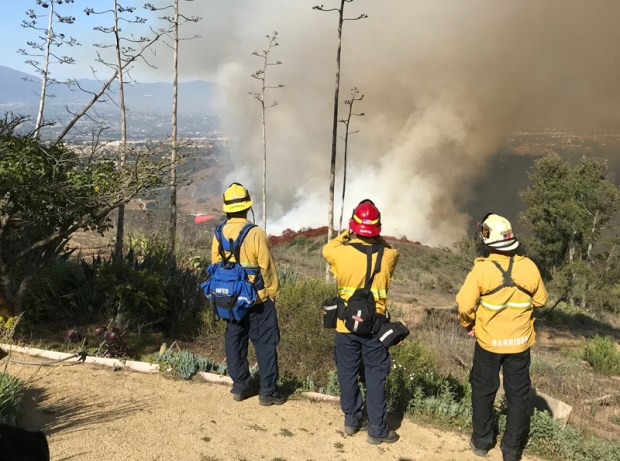 Firefighters attack the blaze from Top of the World on Saturday. (Courtesy of Ken Sadler)