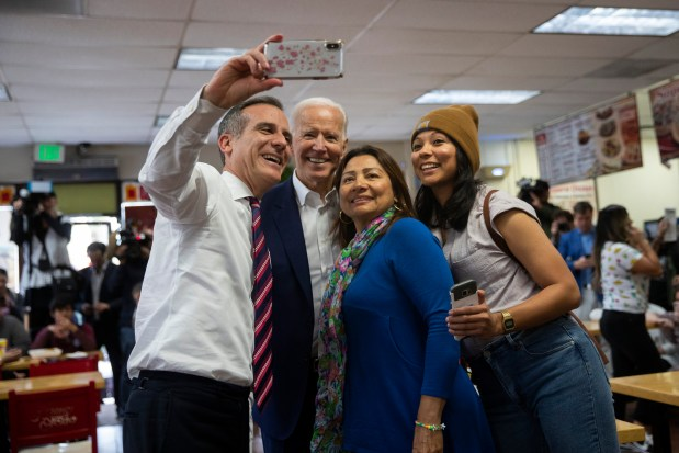 Former vice president and Democratic presidential candidate Joe Biden, second from left, and Los Angeles Mayor Eric Garcetti pause for a selfie with patrons at King Taco Wednesday, May 8, 2019, in Los Angeles. (AP Photo/Jae C. Hong)