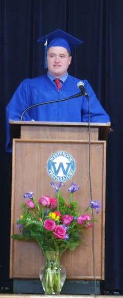 Student in regalia speaking at a podium