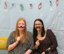 two women with fake mustaches for photo booth