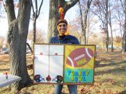 Principal Walia in a turkey hat holding a score board