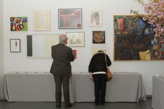 two people looking at hanging art