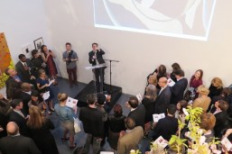 man on small podium surrounded by auction crowd