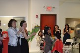women applauding and giving bouquets