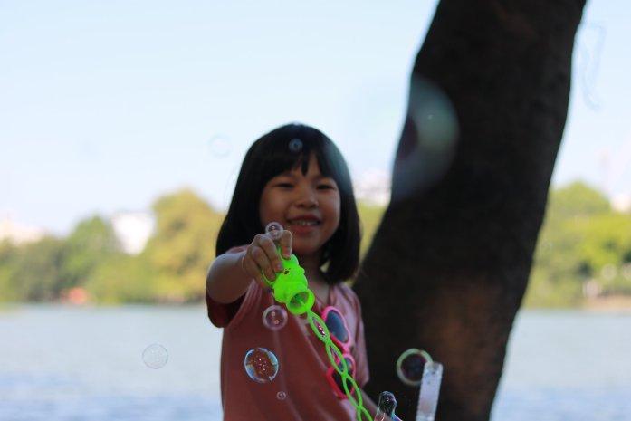 volontariato in laos e cambogia bambina asiatica gioca con le bolle il racconto di viaggio nel sud est asiatico di Giulia Zilibotti