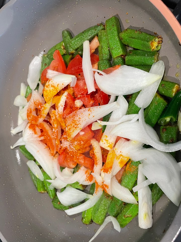 Add the tomato, 1/2 th onion and spices to the salted bhindi