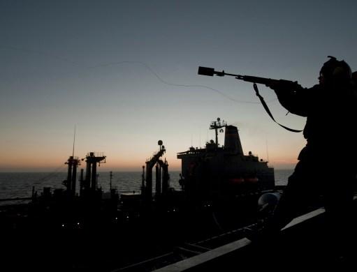 Gunner's Mate 2nd Class John Brown fires a shot line from the carrier Carl Vinson. // MC2 James Evans