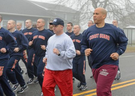 Capt. Todd Prestidge, commanding officer of Training Center Cape May, N.J., center, runs alongside  Sen. Cory Booker, D-N.J., and recruits of Foxtrot and Golf companies 189 at the training center on Saturday. (Coast Guard photo by CWO Donnie Brzuska)