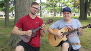student and teacher outside playing guitars