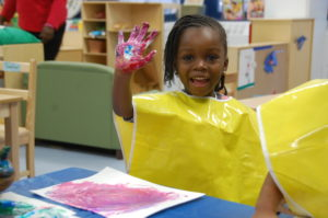 Young girl holding up her painted hand from fingerpainting