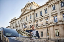 Medium shot of a smiling middle-aged male driver leaning on his car while parking in front of an ornate building in Poland