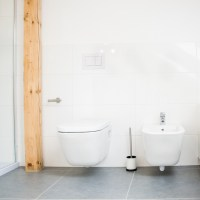 A bidet and a toilet in a modern bathroom.